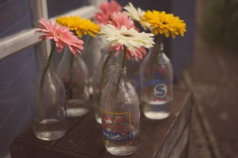 gerbera wedding flowers in vintage milk bottles © - Christy Blanch Photography / French Wedding Style Blog