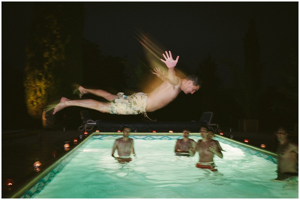 groom flying through the air before pool