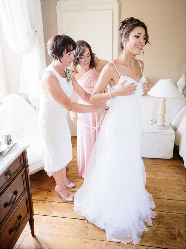 Mother of the bride and Bridesmaid fastening the brides dress