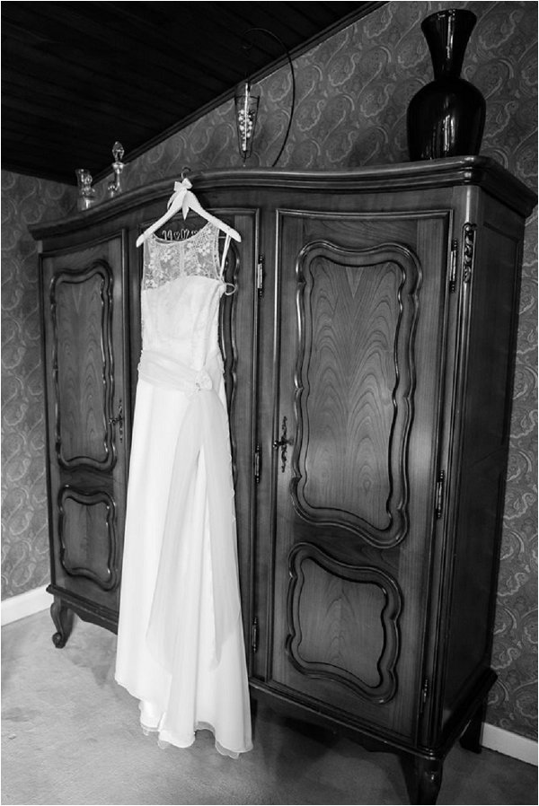 Bridal gown with bow detail hanging on wardrobe