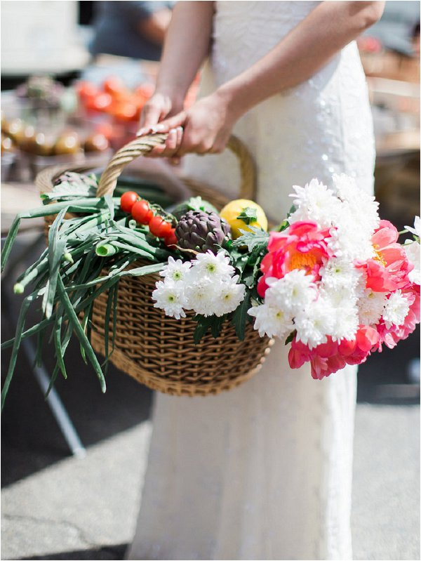 Bride carries basket of fresh local produce in Provence