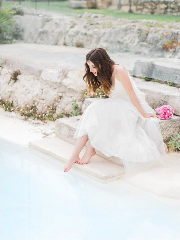 Bride dipping her toe into the swimming pool at Mas de la Rose in Provence