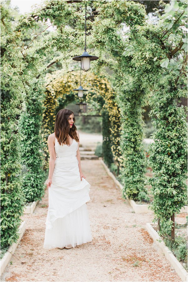 Bride poses under a wonderful flower arch in Provence