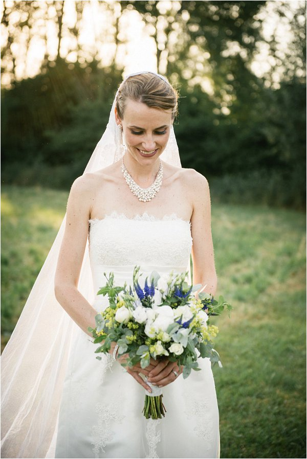 Blushing bride holding her white and blue bouquet