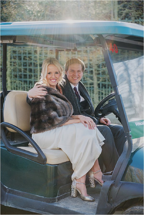 Bride and Groom pose on a golf buggy
