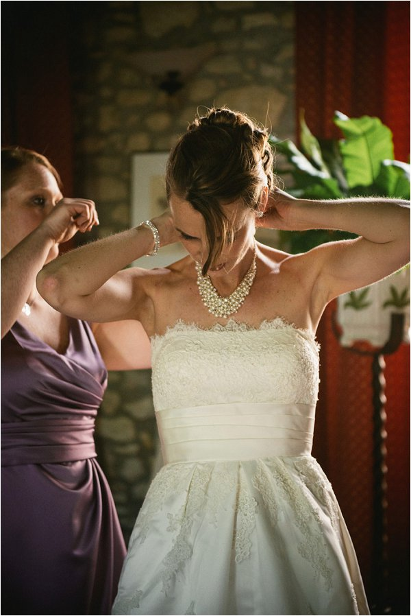 Bride fastens her pearl beaded necklace