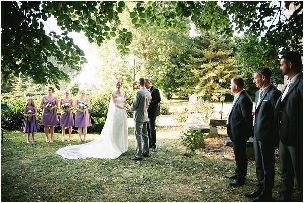 Bridesmaids and Groomsmen observe the vows