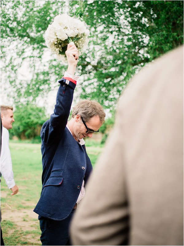 Delighted male wedding guest catches the bouquet