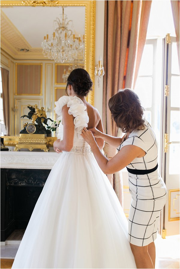 Fastening the buttons on one shouldered wedding gown