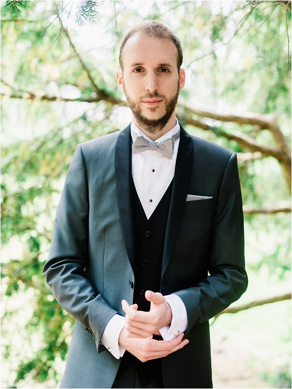 Groom in grey and black suit complete with silver bow tie