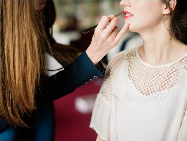 Make up artist applies brides ruby red lipstick