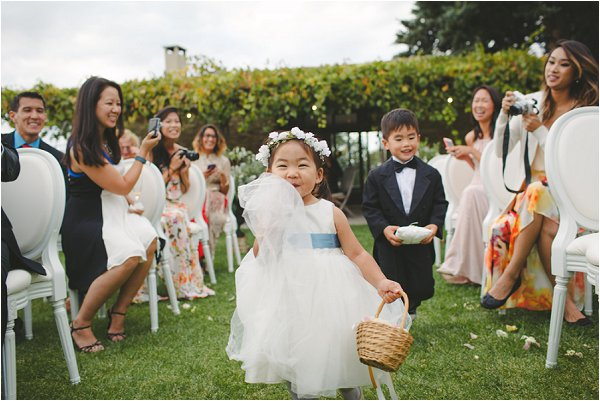 Adorable flower girl and page boy walking down the aisle