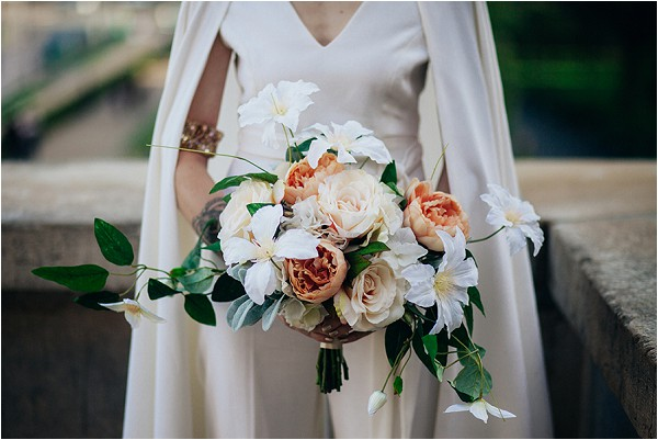 bride in cape with oversize bouquet