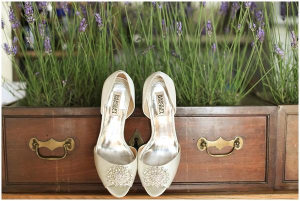 White Badgley Mischka bridal shoes set against lavender