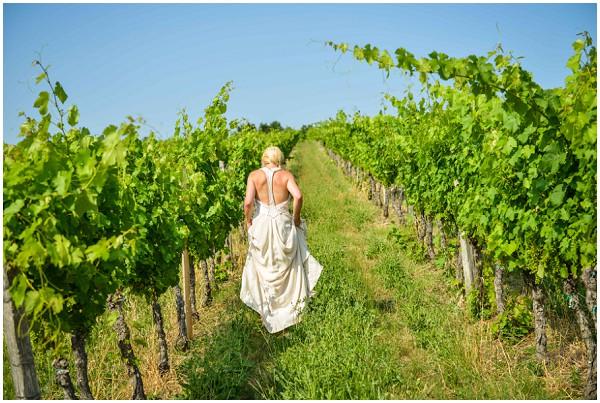 bride walking through vineyards
