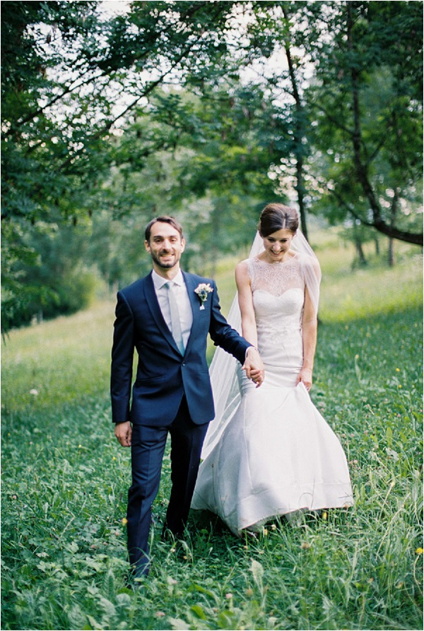 couple walking with groom looking at camera