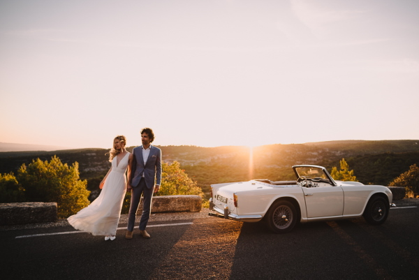 Bride and Groom by white wedding car in sunset