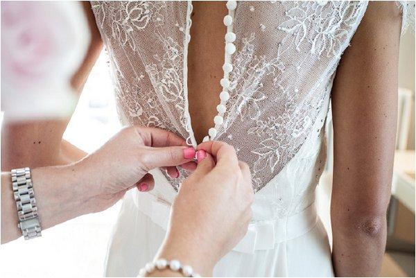 bridesmaid buttoning wedding dress