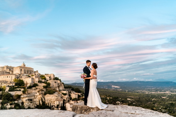 Bride and groom look at each other in front of blue sky and french vista