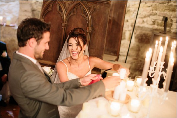 Bride and Groom lighting wedding candles in Chateau cellar