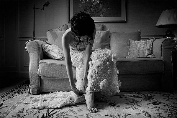 Bride wearing Lazaro gown and fastening her heels