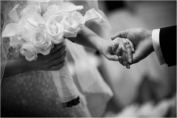 Elegant white roses, holding hands and a stunning wedding ring
