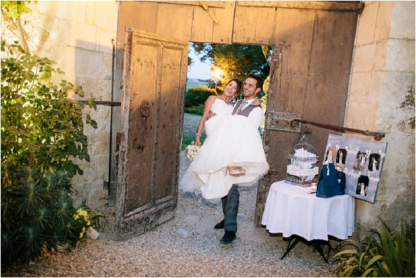 Groom carrying the bride over the threshold