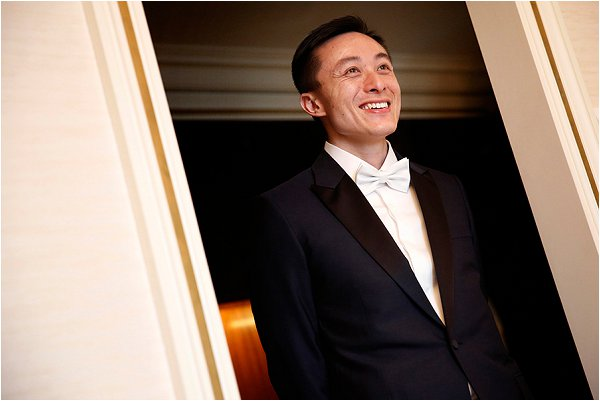 Handsome groom wearing Dior Homme Tux and white bow tie