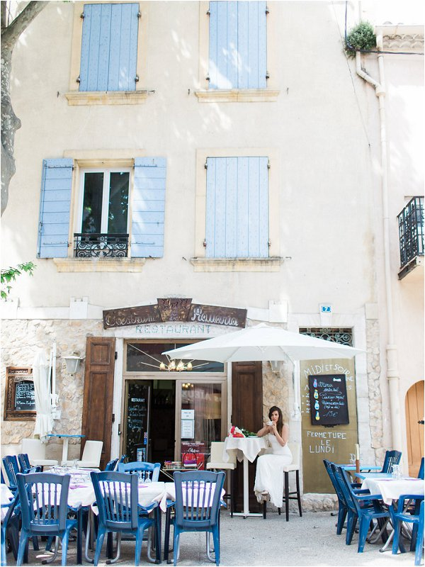 Bride enjoying a coffee and watching the world go by in traditional French village