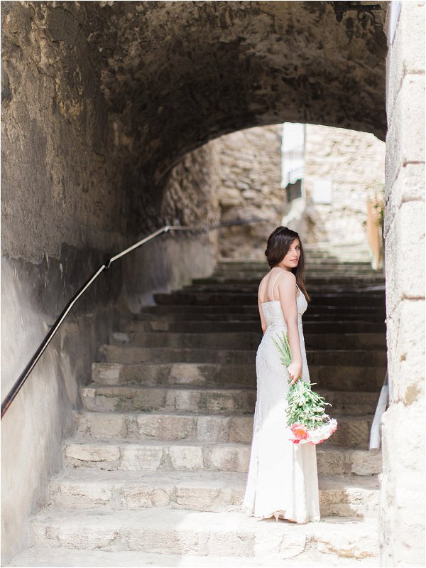 Bride posing under traditional stone archway in Provence inspiration shoot