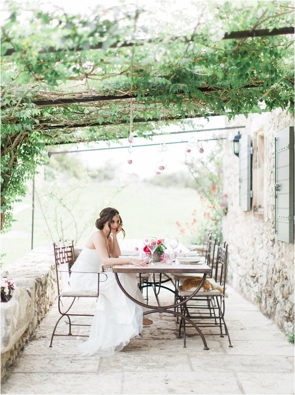 Bride relaxing under a grape vine archway in Provence Wedding Inspiration shoot