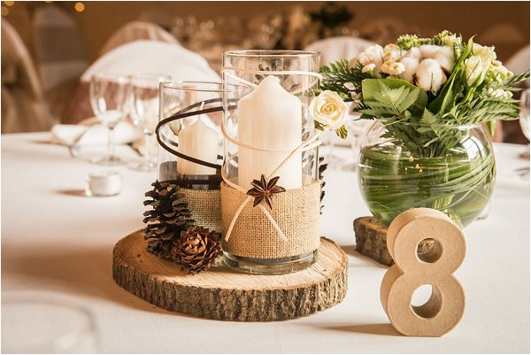 Table centrepiece featuring real logs pince cones and neutral candles