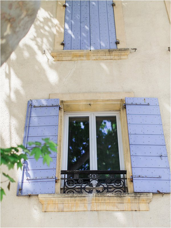 Traditional blue shutters on the side of French village house