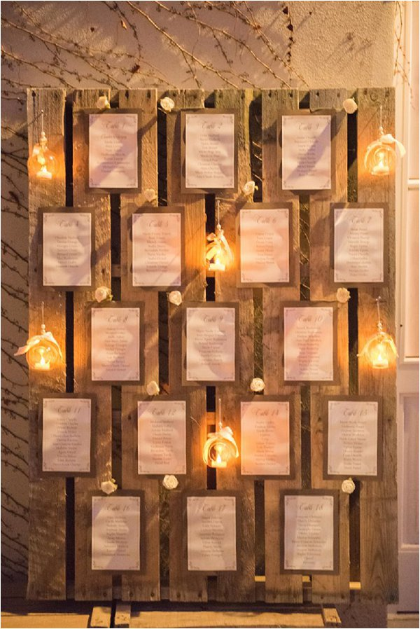 Winter wedding table plan decorated with golden tea lights