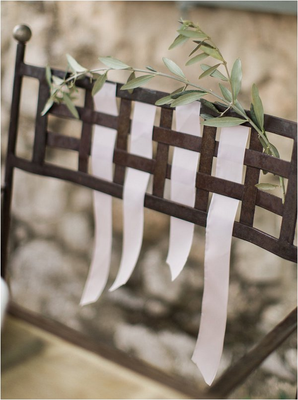 Wrought iron chairs dressed with ribbons and olive branches in Provence Wedding photo shoot