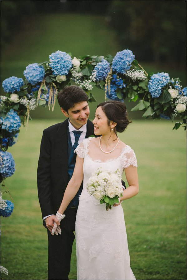 Bride and Groom pose under blue and white flower arch