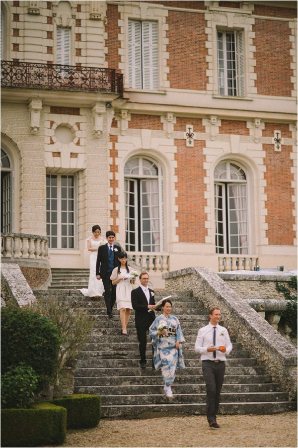 Bride and groom walking down the steps at Chateau de Baronville