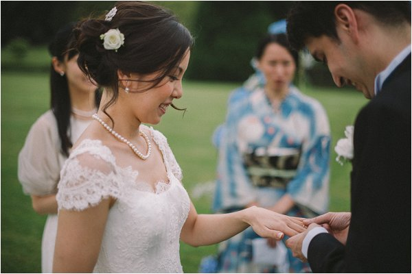 Exchanging rings in outdoor ceremony at Chateau de Baronville