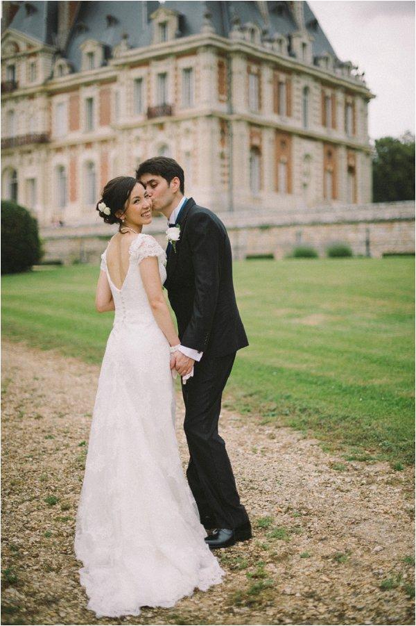 Happy Bride and Groom pose outside Chateau de Baronville