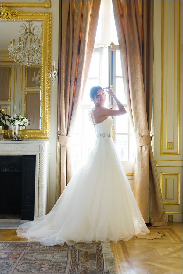 Beautiful bride poses in her drress in front of the Chateau windows