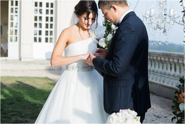 Bride and Groom exchange rings in outdoor ceremony