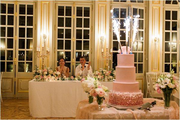 Bride and groom enjoy sparklers on pastel pink cake