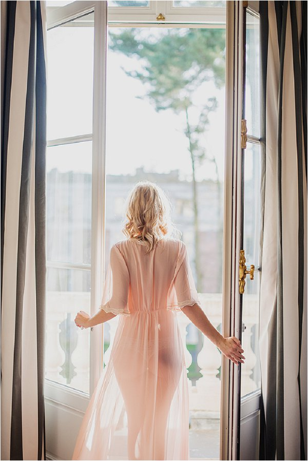 Bride wearing pink BHLDN Robe on hotel balcony