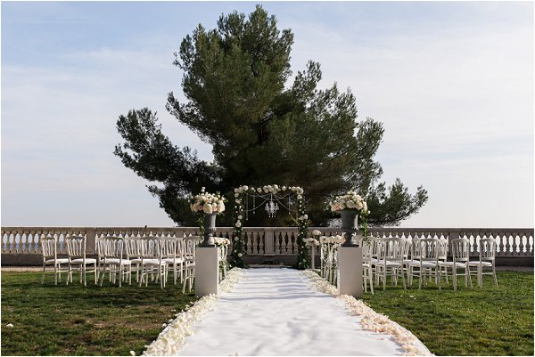 Outdoor wedding aisle complete with archway and rose petals