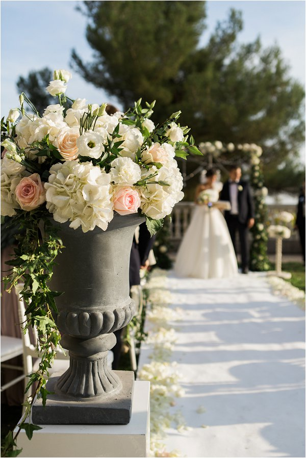 Pastel flowers in urn decorate the aisle