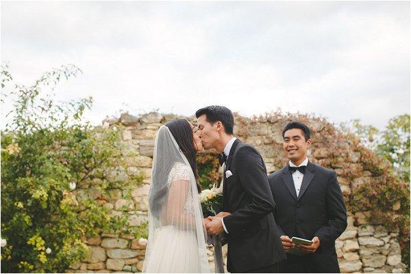 Handsome tuxedo clas groom kisses his bride