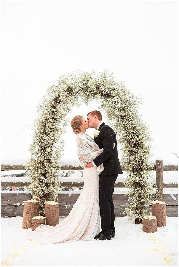 newly weds kissing under a beautiful arc of snow and flowers