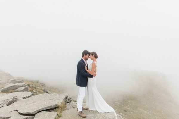 newly wed couple kiss on misty cliff top