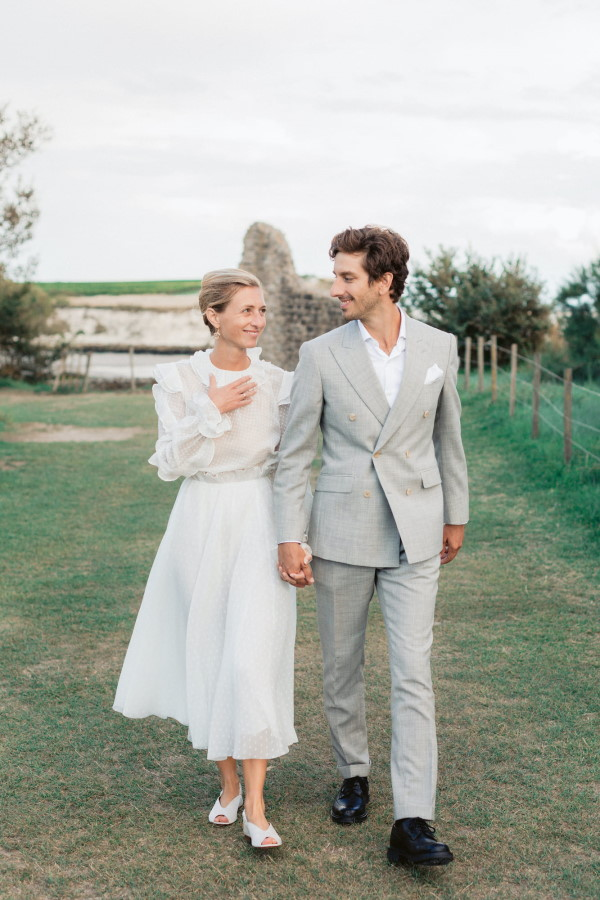 bride in 3/4 length dress and groom in gray suit walk holding hands