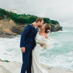 bride and groom kiss next to blue foamy ocean